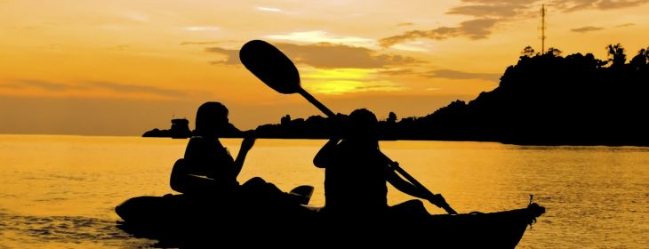 Silhouette of Two person kayaking in the sea