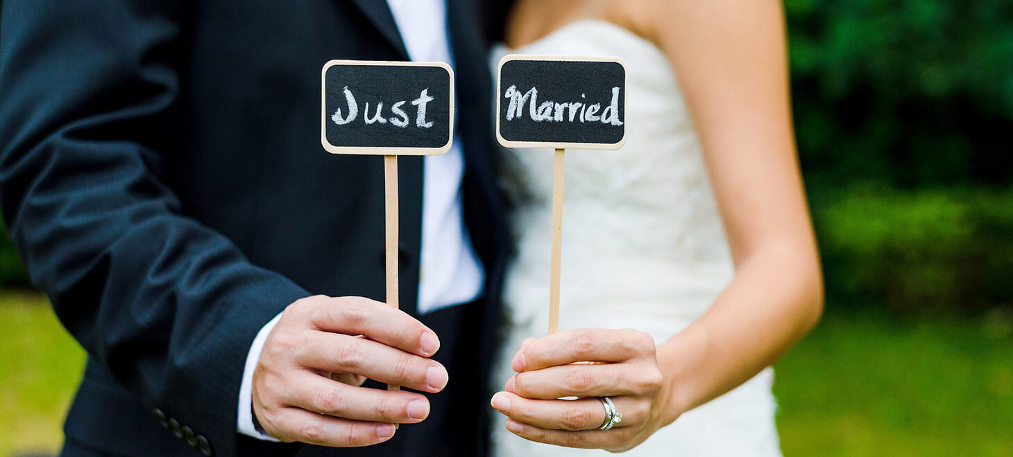 "Bride and groom holding up signs that say ""Just Married"""