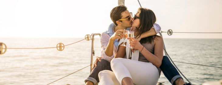 Couple sitting on a yacht kissing and holding glasses of Champagne