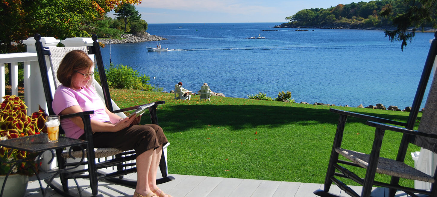 Woman reading a book in a chair with view of water